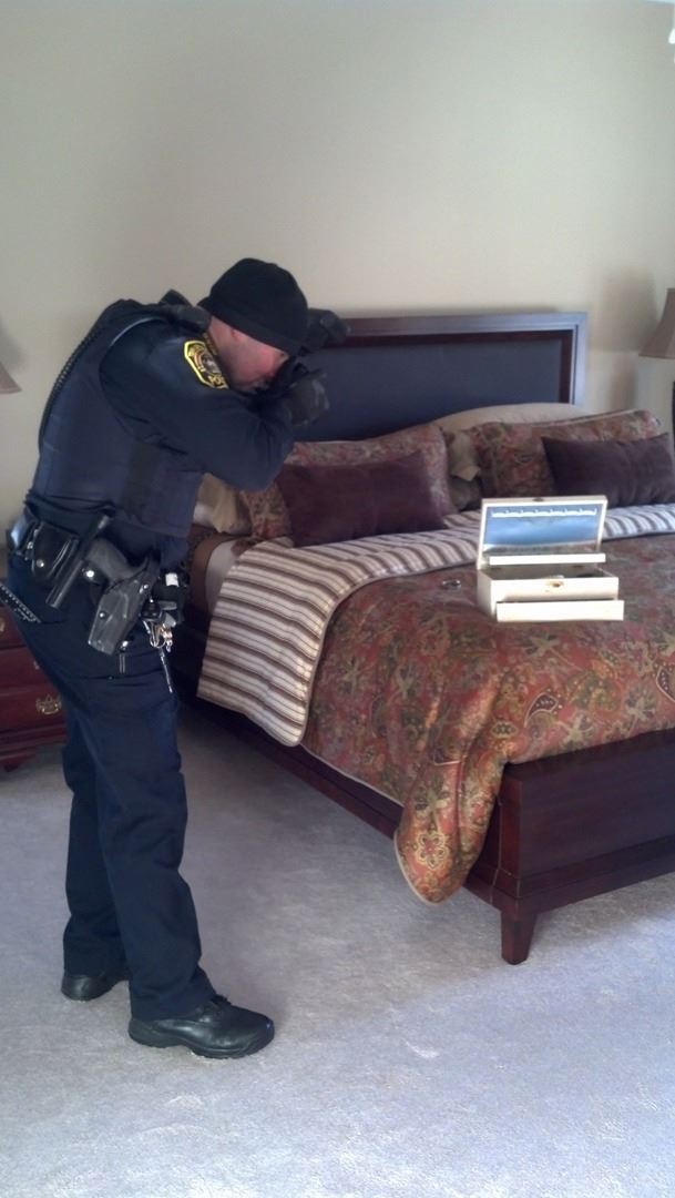An evidence technician takes pictures in a bedroom