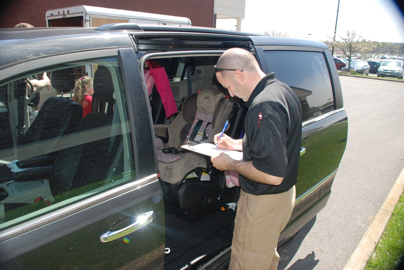 A technician inspects a child safety seat for proper installation